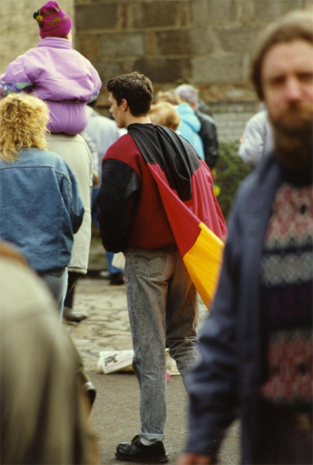 Geschichte wird gemacht: Mann mit Deutschlandflagge beim Straßenfest anlässlich der Öffnung des Grenzübergangs Oranienburger Chaussee/Berliner Straße, März 1990. Wer sich nicht an die Vergangenheit erinnern kann, ist dazu verdammt, sie zu wiederholen. Zeitzeugen bringen Nachgeborenen das Erlebte näher. In: Prinzip Apfelbaum. Magazin über das, was bleibt. Foto: Ralf Skiba/CC BY-NC-ND