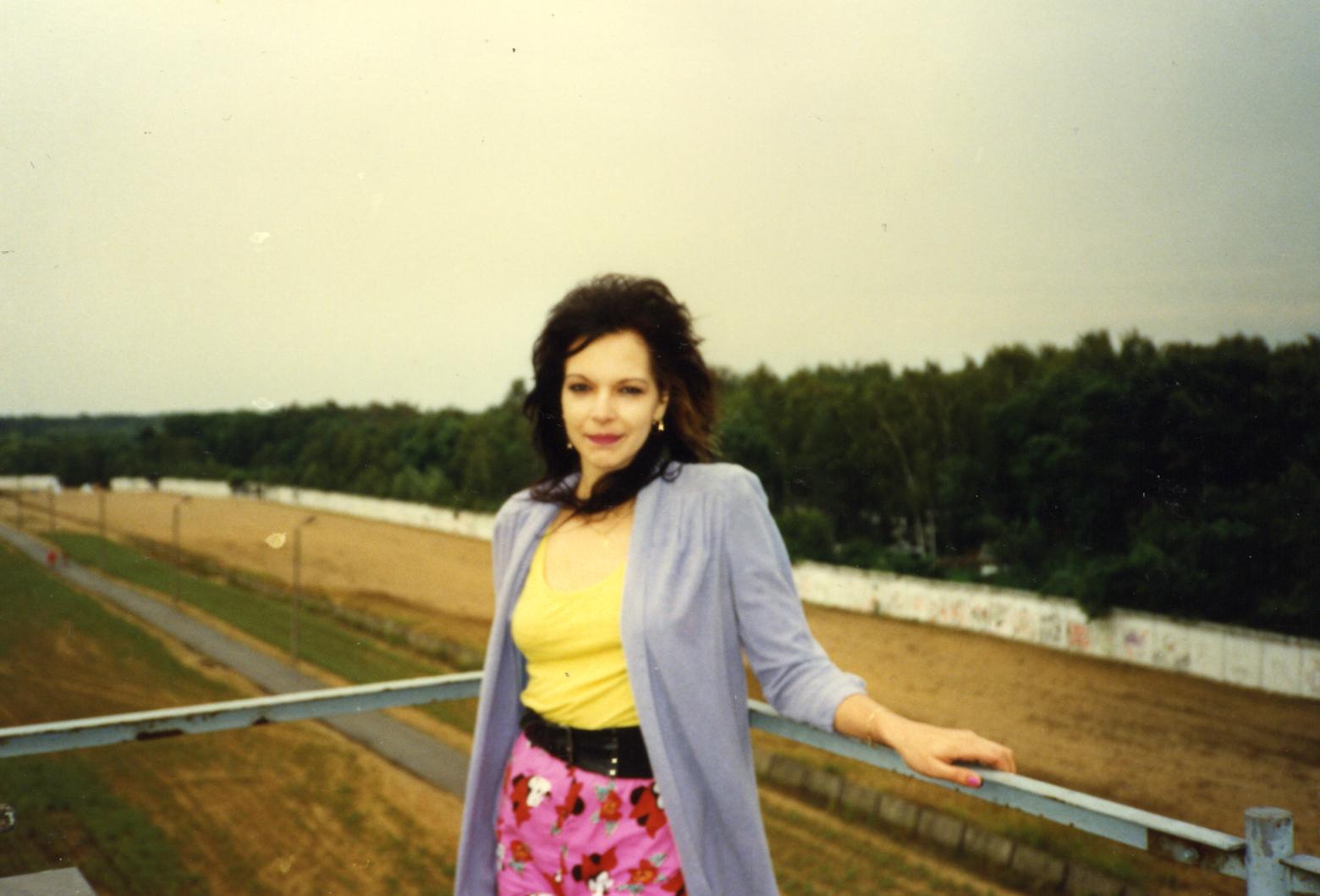 Geschichte wird gemacht: Eine junge Frau posiert vor dem Grenzstreifen der Berliner Mauer bei Gatow, August 1990. Das Wissen über unsere Herkunft hilft, gesellschaftliche Zusammenhänge zu verstehen. Zeitzeugen bringen das Erlebte näher. In: Prinzip Apfelbaum. Magazin über das, was bleibt. Foto: Viola Kaffke/CC BY-NC-ND