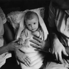 Prinzip Apfelbaum. Magazin über das, was bleibt. Ausgabe 14: VERTRAUEN. USA. New Rochelle, NY. 1953: Ein Kleinkind, gehalten von Vater und Mutter. Symbolbild. Vertrauen ist die Basis für den Zusammenhalt, stärkt Bindungen, schafft Einigkeit. Auch wer mit dem Erbe Gutes tun möchte, braucht Vertrauen. Foto: Eliott Erwitt / Magnum Photos / Agentur Focus