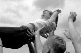 Vertraut euch: Eine junge Frau lässt sich von einer Gruppe auf Hände tragen. Symbolbild. Wer vertraut, riskiert enttäuscht zu werden. Doch das Wagnis lohnt. Denn Vertrauen ist ansteckend. In: Prinzip Apfelbaum. Magazin über das, was bleibt. Foto: pinky/photocase.de