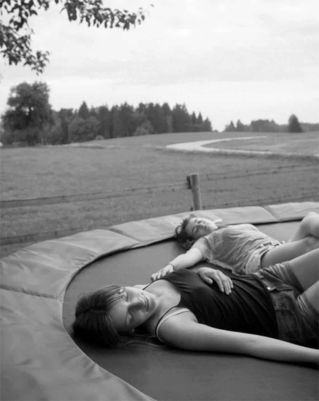 Vertraut euch: Zwei Mädchen liegen entspannt auf einem Trampolin. Symbolbild. Wer sich für vertrauenswürdig hält, dem wird auch eher Vertrauen entgegengebracht. In: Prinzip Apfelbaum. Magazin über das, was bleibt. Foto: bit.it/photocase.de