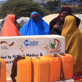 Frauen mit Wasserkaninstern an einem Brunnen in Somalia