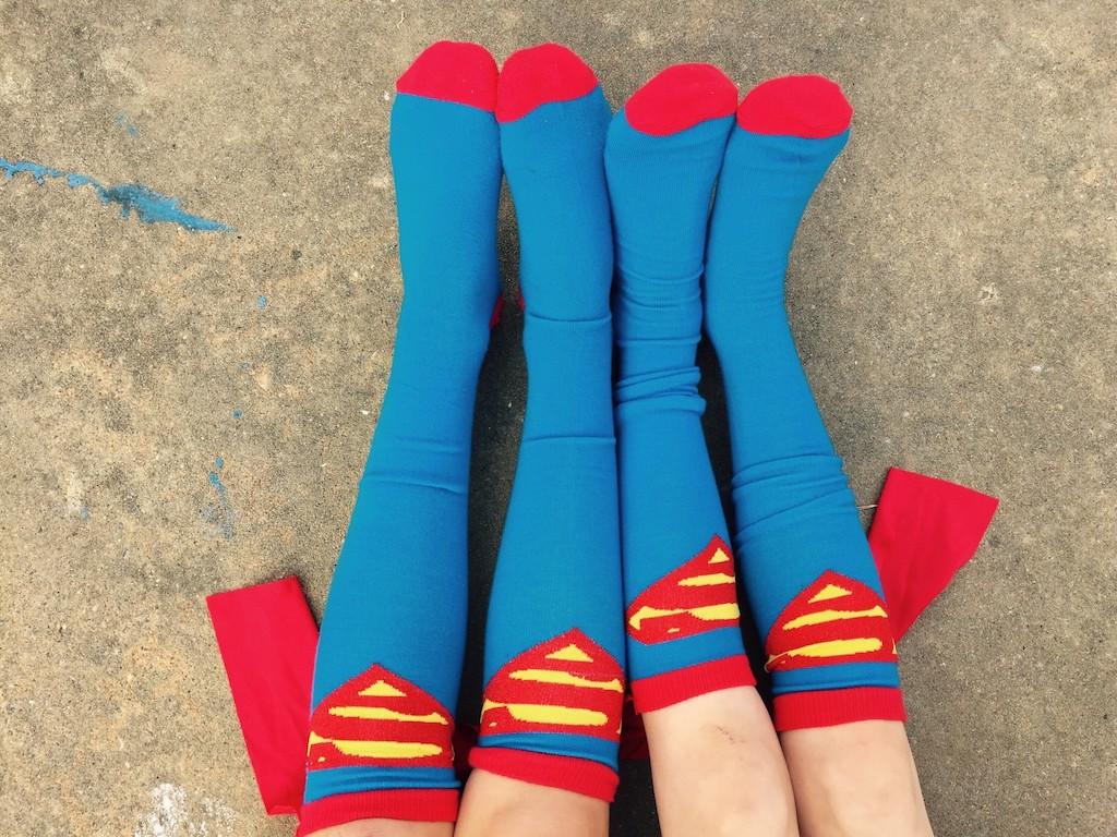 Kuschelnde Beine stecken in Superman-Socken: Heldentaten wirken ansteckend.