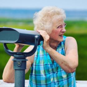 Eine ältere Frau steht an einem Fernrohr im Grünen: im Alter einen neuen Lebenssinn finden.
