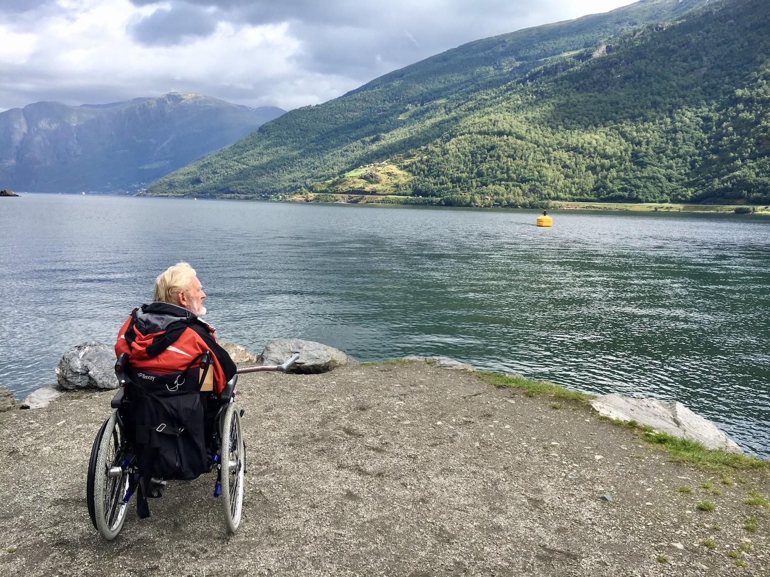 Ein weißhaariger Tourist im Rollstuhl blickt auf einen Fjord: Vergangenheit loslassen, Zukunft gestalten.