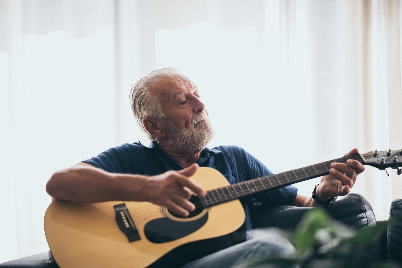 Ein weißhaariger Mann spielt Gitarre. Ein Musikinstrument zu spielen, trainiert das Gehirn.