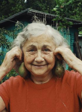 Eine Frau hält sich mit einem Lächeln Birnen an die Ohren. Es braucht Mut, glücklich zu sein.