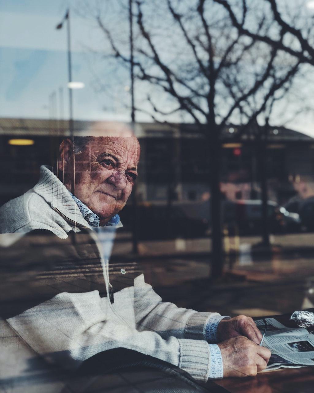 Ein alter Mann blickt nachdenklich durch die Scheibe eines Cafés: Was schützt vor Reue?