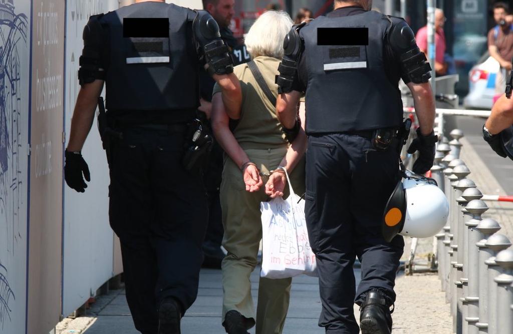 Zwei Polizisten haben Irmela Mensah-Schramm von hinten Handschellen angelegt und führen sie ab.