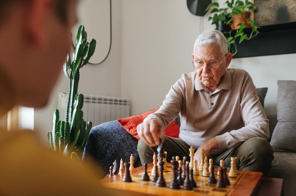 Ein junger und ein alter Mann spielen Schach. Ältere können viel Wissen und Erfahrungen weitergeben.