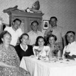 Die Familie versammelt sich am Esstisch – seit Generationen, wie das alte Schwarz-Weiß-Foto zeigt.