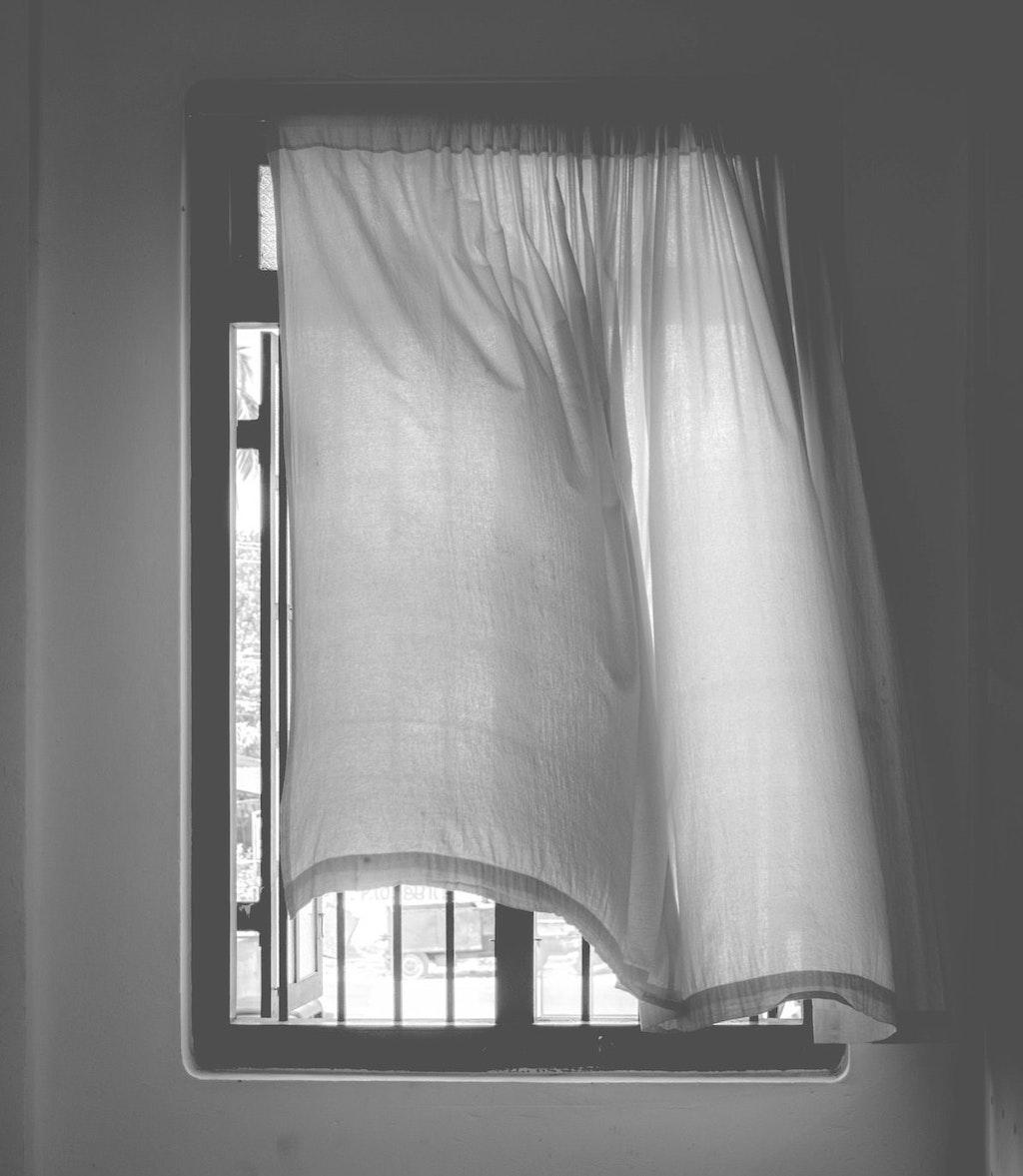 Vergessene Rituale: Vor einem offenen Fenster weht ein Gardine im Wind.