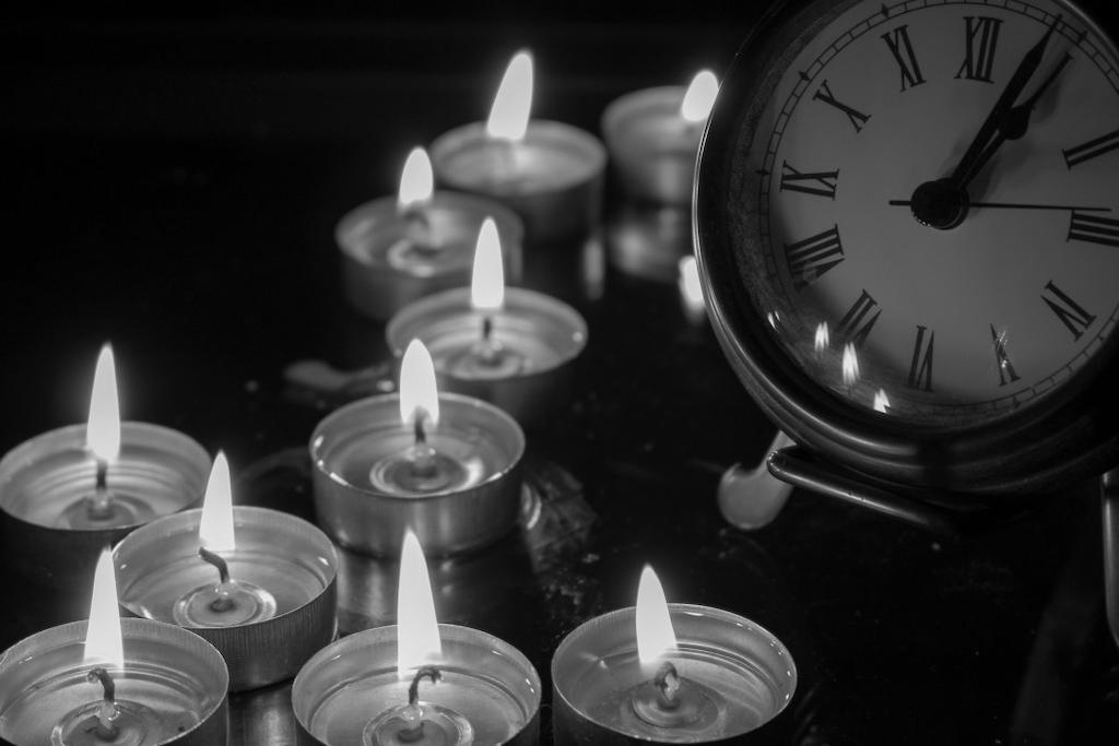 Vergessene Rituale: Kerzen stehen vor einem alten Wecker.
