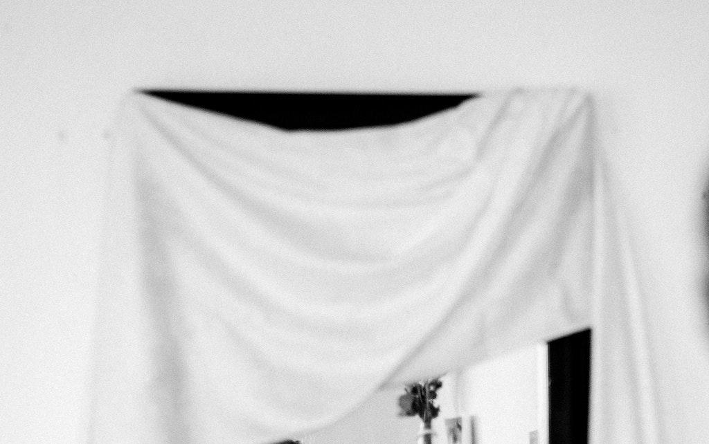 Vergessene Rituale: Ein Laken ist über den Spiegel gelegt.