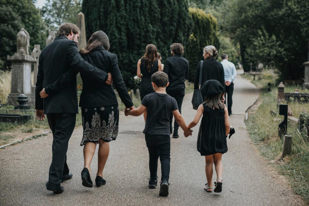 Eine Familie geht nach der Beisetzung über den Friedhof: Rituale des Abschieds.