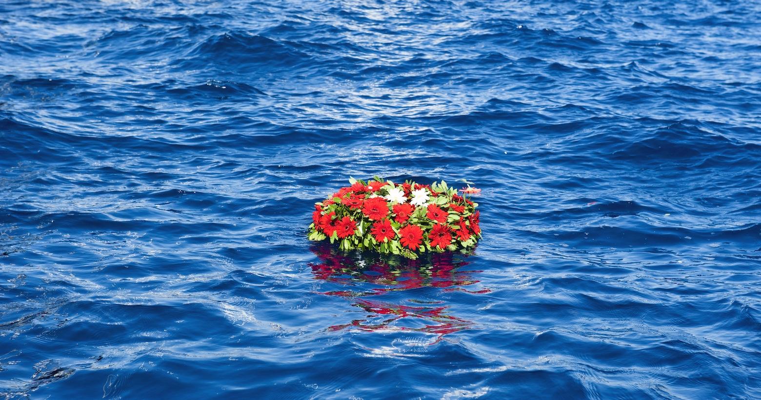 Eine Seebestattung: Ein Blumenkranz schwimmt auf dem Meer.
