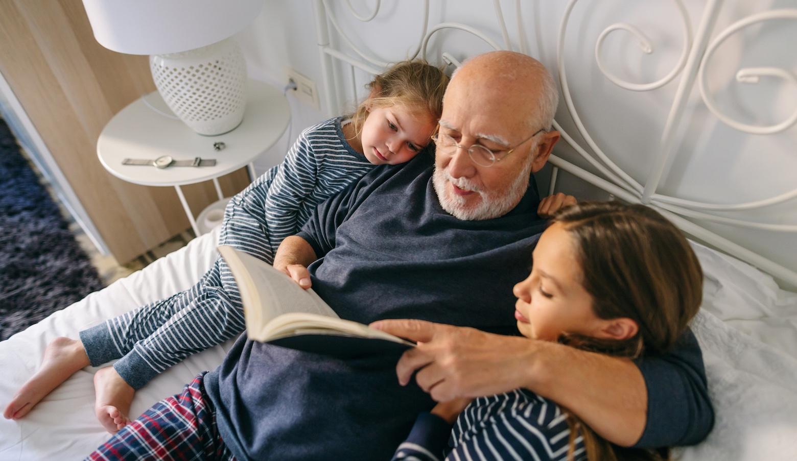 Bettrituale: Ein Großvater liest seinen Ekelkindern im Bett ein Buch vor.